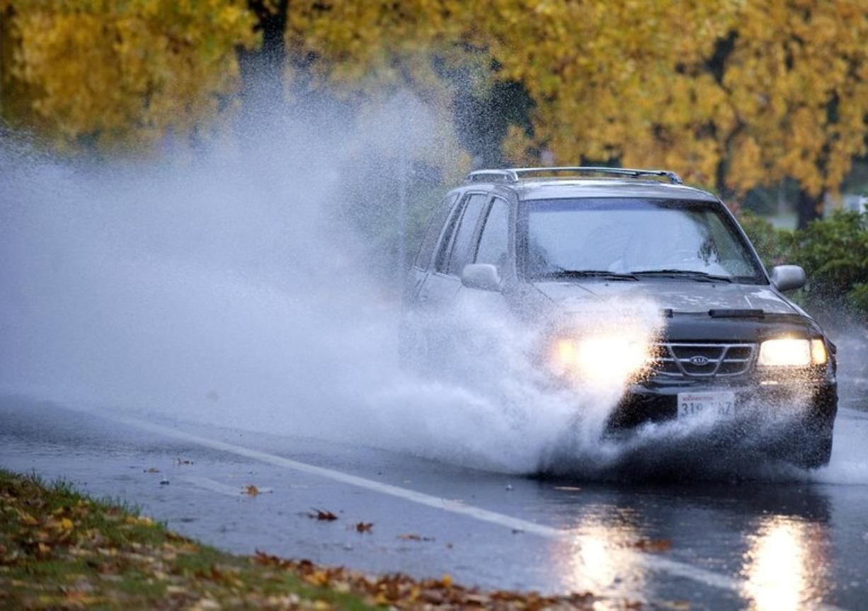 Photos by Zachary Kaufman/The Columbian A vehicle blasts through standing water on East Mill Plain Boulevard near Hudson's Bay High School during a downpour Monday morning. Top: Marine biology major Brian Anderson, 22, of Vancouver walks across the Clark College campus.