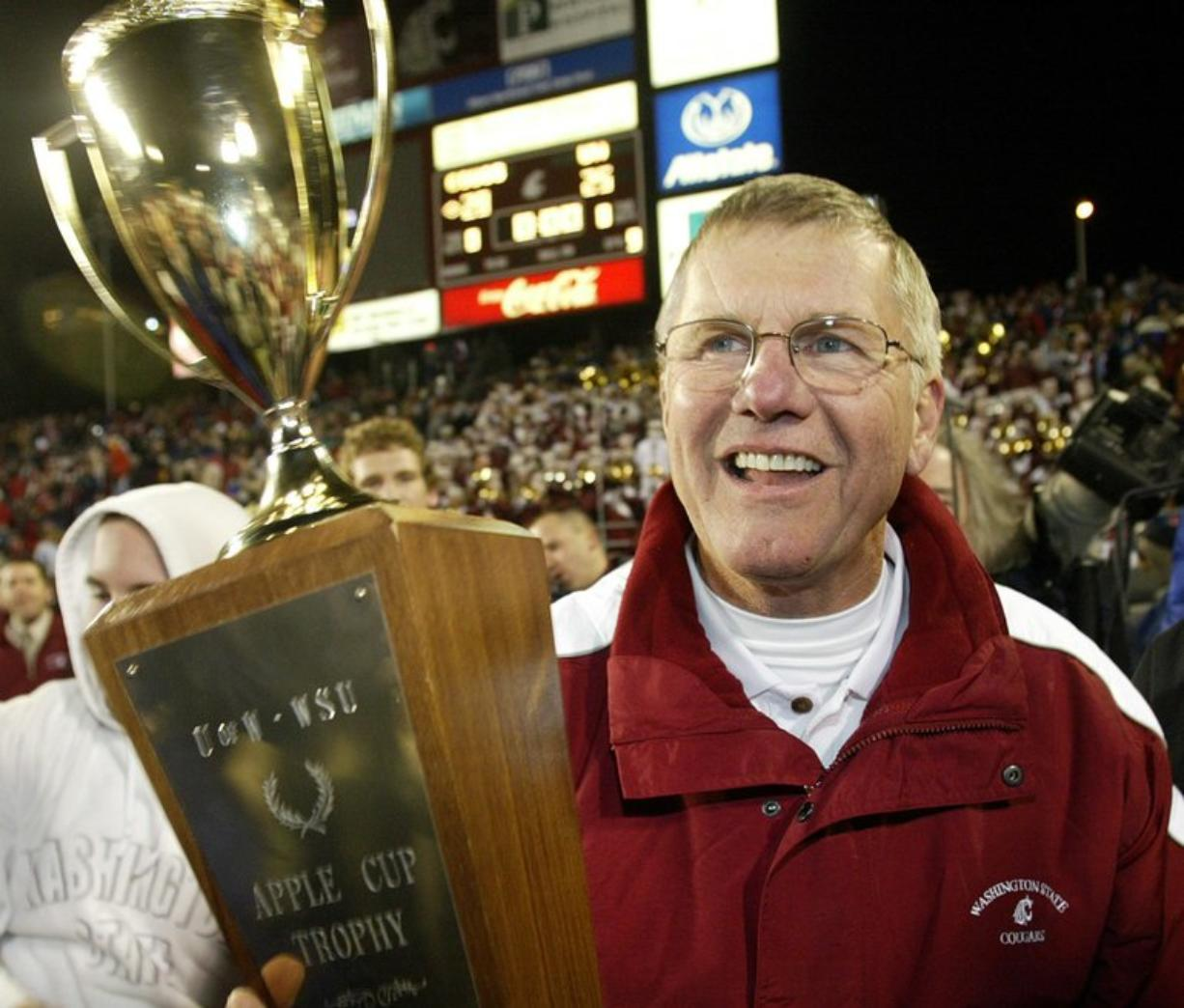 ** FILE ** Washington State head coach Bill Doba holds the Apple Cup trophy after his team beat Washington 28-25 in this Nov. 20, 2004, file photo in Pullman, Wash. Doba is looking for a little consistency this season after last year's team was slowed by injuries and inexperience and fell to a 5-6 record. (AP Photo/Ted S.