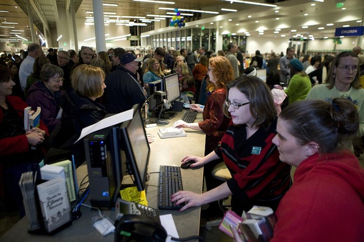 Megan Dugan, second from right, a circulation clerk, helps Heather Cyr, right, hceck out books after the Cascade Park Community Library grand opening on Tuesday. There also are several self-check stands, and an automated return facility visible from the lobby.