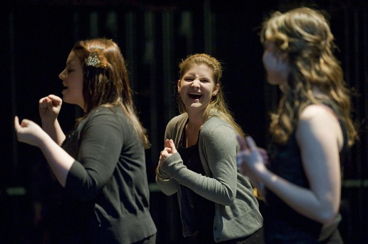 "Makayla Plock, 16, left, Alysha Mueller, 16, and Caitlin Moore, 16, sign ""Stop! In the Name of Love"" by The Supremes while rehearsing for a show Thursday at Camas High School. The show, ""A Helping Hand,"" will raise money for deaf children in the African country of Zambia."