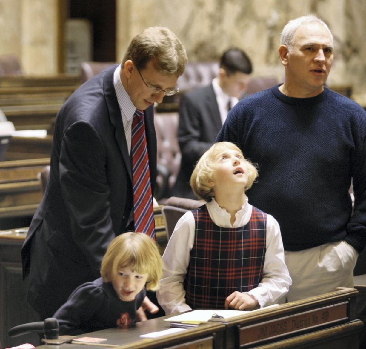Rep. Jim Jacks, D-Vancouver, shows his daughters, Sara, 5, left, and Hannah, 8, around his desk on the House floor on the opening day of the 2009 session of the Washington Legislature at the Capitol in Olympia.