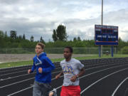 Ridgefield sophomore Silas Griffith, right, runs with teammate Ciarnin McNeil during a recent track practice.