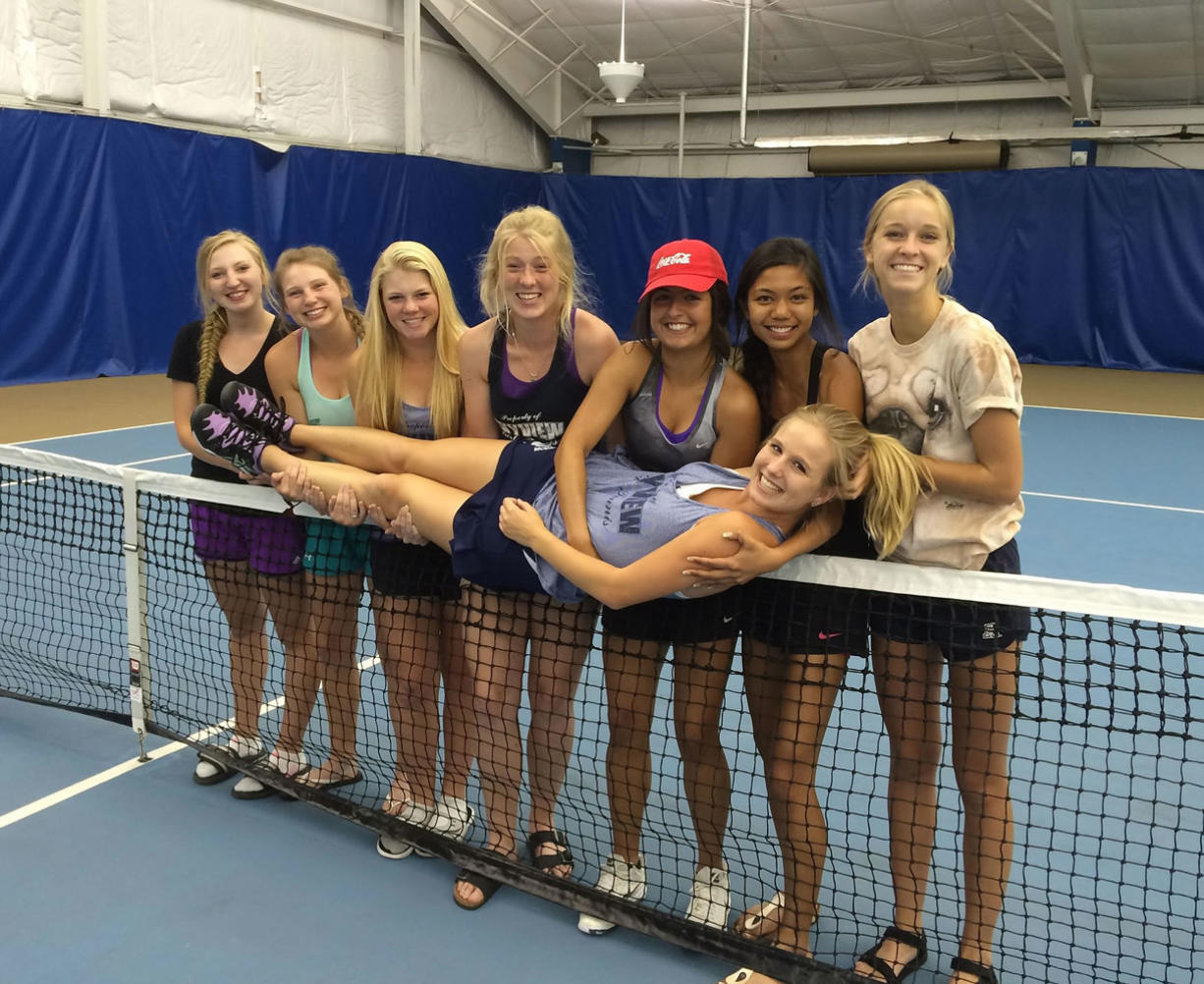 Skyview teammates hold up senior Sammi Hampton on the net on Saturday at the Columbia Basin Racquet Club in Richland after Hampton was declared the Class 4A singles champion for a fourth year in a row.