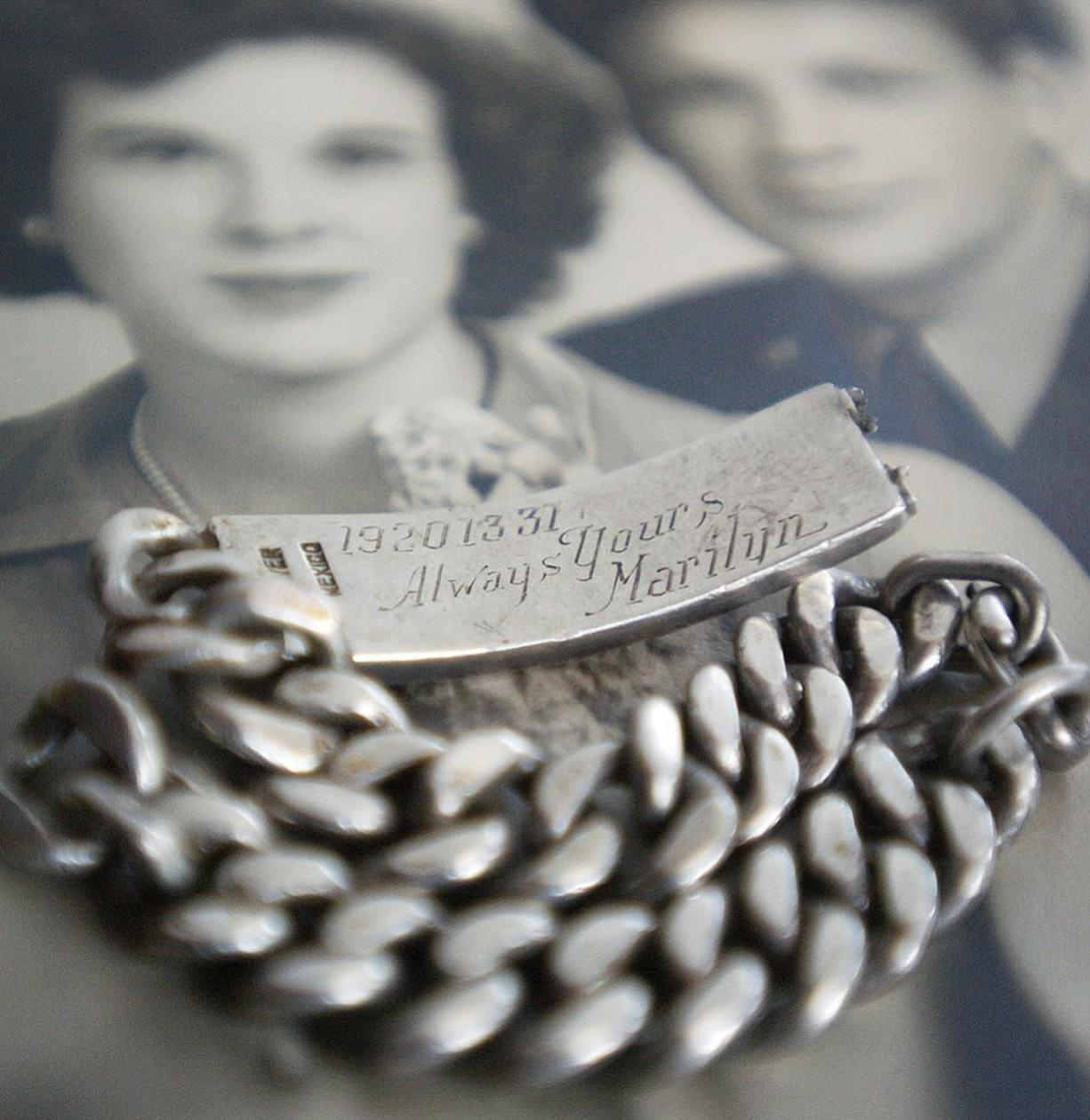 A bracelet given to airman Steve Memovich by his wife, Marilyn, was lost for decades. Here, it sits on a portrait of the couple from the 1940s.