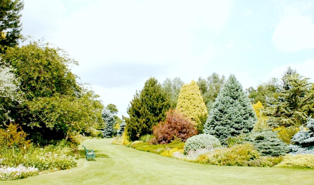 ROBB ROSSER Plant-filled borders are perfectly framed by a lush, well-mown lawn.