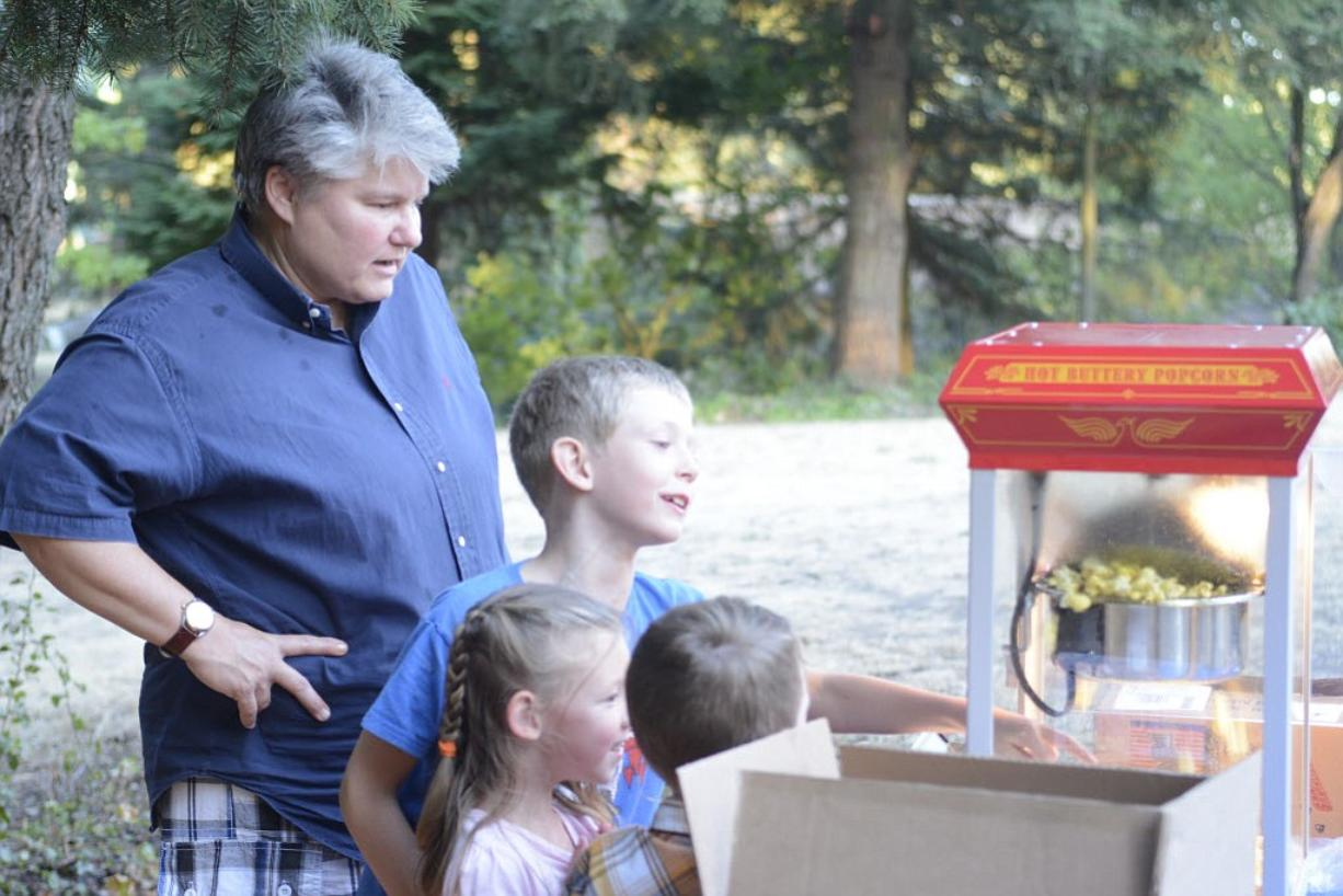 """Colleen Neel makes popcorn for a crowd that gathered at Water Works Park to watch """"The LEGO Movie"""" on Friday."""