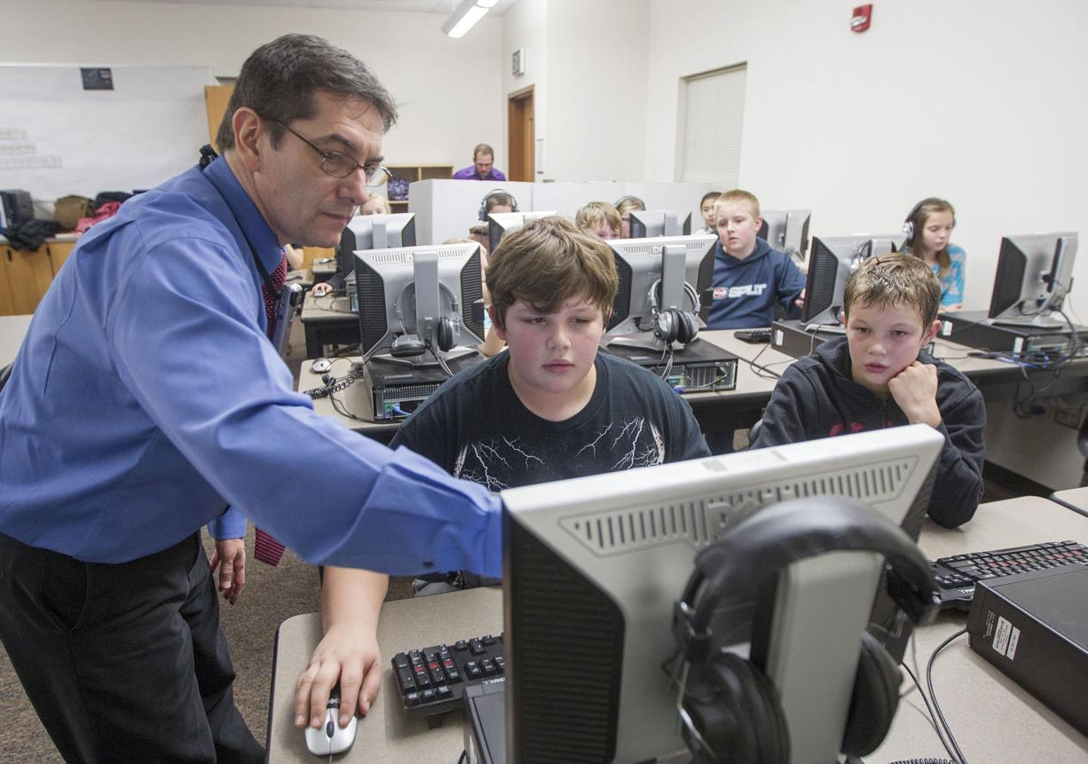 Frederick Tillman, computer teacher at Amboy Middle School, left, helps sixth-grader Ely Earl, center, in an Hour of Code puzzle.