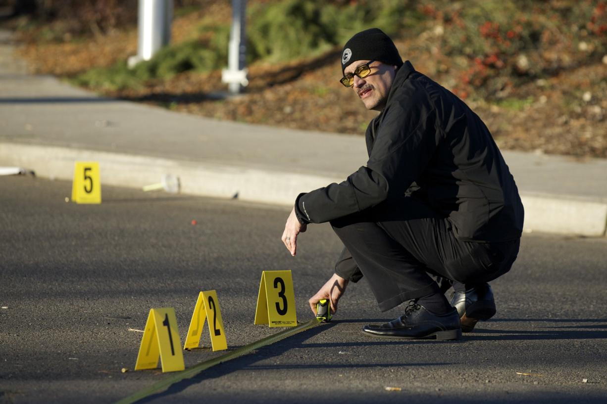 Vancouver police detective Lawrence Zapata investigates shell casings near the intersection of 33rd Street and St.