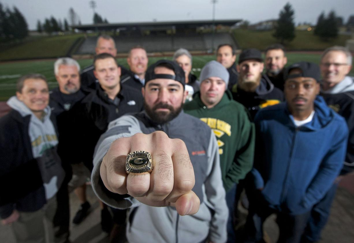 Nick Fleck, quarterback of the Evergreen High School football team in 2004, holds out his state championship ring with other members of the team and coaching staff.