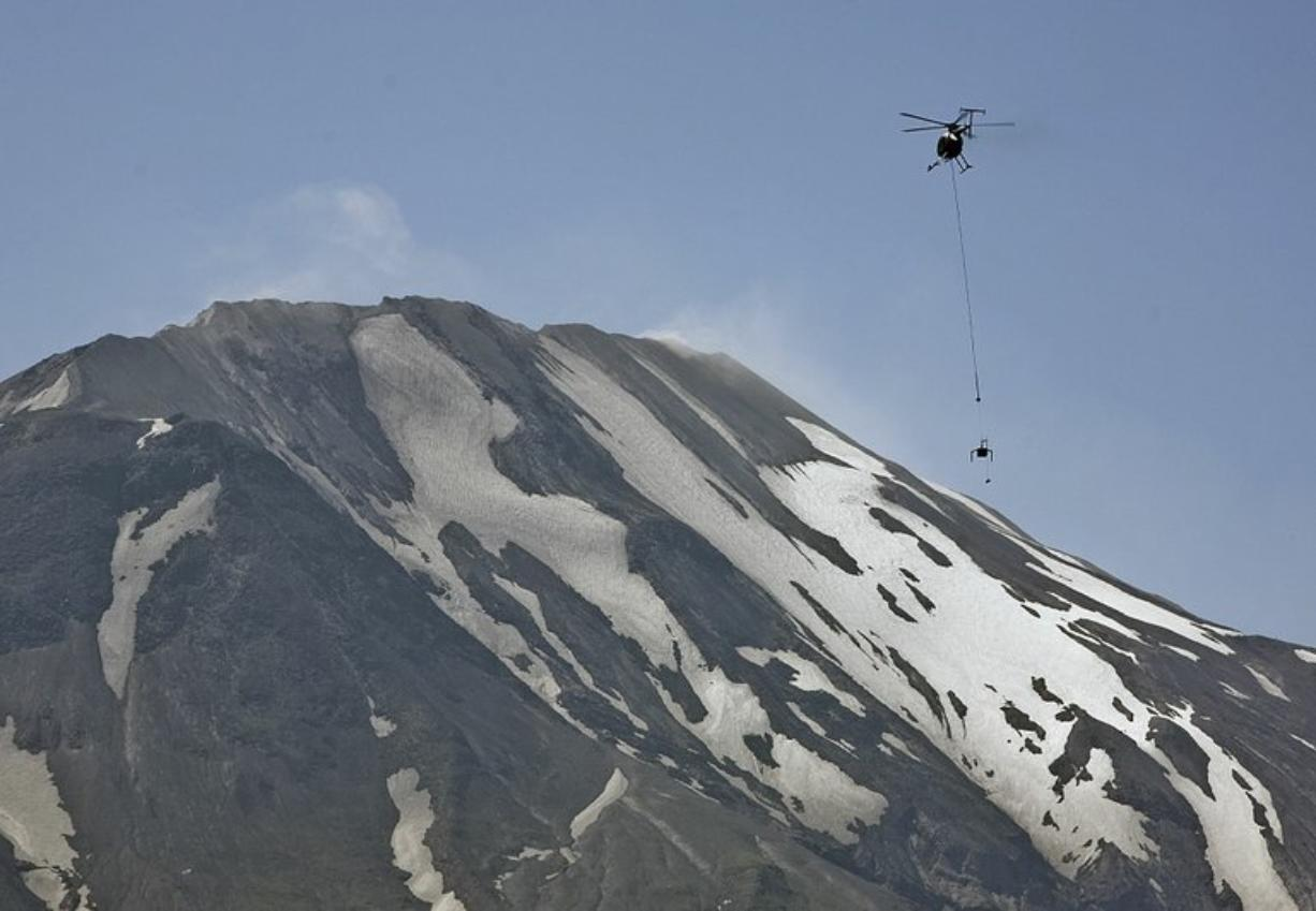 """A team of USGS scientists used a helicopter to deploy their advanced """"spider"""" sensors to the Mount St. Helens crater in July 2009. The spiders are designed to collect important information from dangerous situations such as volcanoes and possibly other planets. (Columbian files)"""