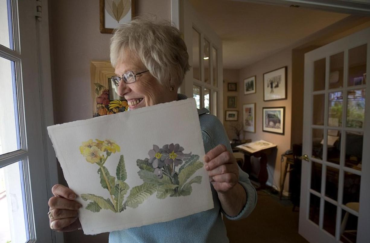 Artist Marilyn Wood Bolles holds one of her paintings.