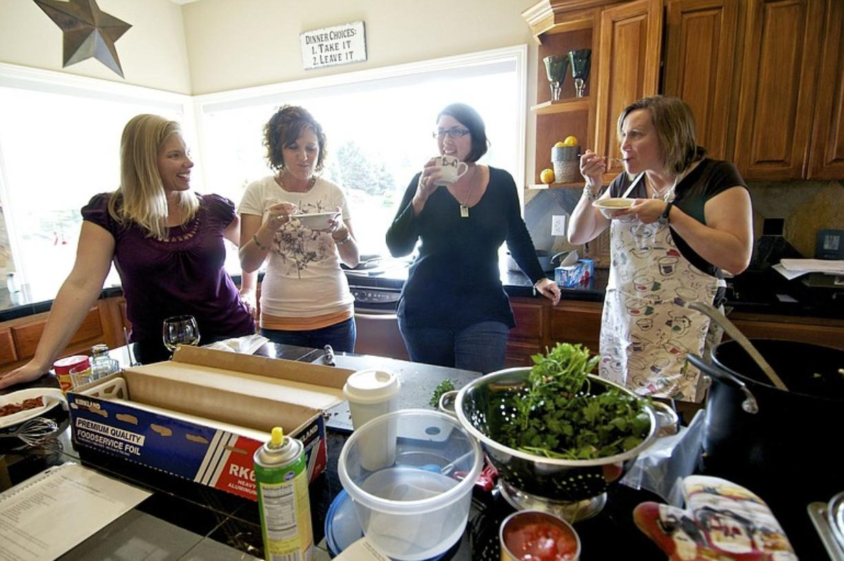 Amy Benson, left, Debbie Oster, Krista Colvin and Angela Fadlovich share a moment together during a cooking party for the Colvin family as a way to support Krista as she undergoes treatment for breast cancer.