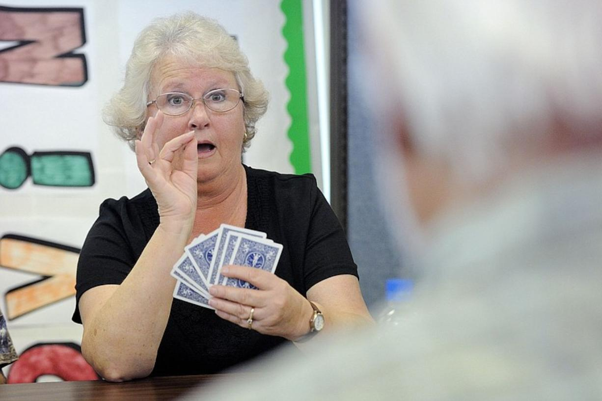 Melinda Schreiner converses in American Sign Language with Dwight Mackey, foreground, during a recent card game that was part of a recreation session for seniors at Southwest Washington Center of the Deaf and Hard of Hearing, now permanently housed in what used to be the Cascade Park Community Library.