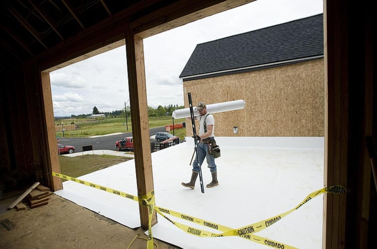 Marshall Hatfield from JXL Siding walks on a rooftop deck Monday that will become a semi-private courtyard for a Ridgefield home that will be showcased at the Parade of Homes in July.