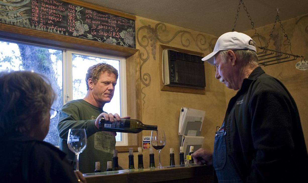 Wind River Cellars owner Joel Goodwillie, center, pours Allen and Jean Yanity, of Lake Bay a glass of wine inside the tasting room in Husum on May 19.
