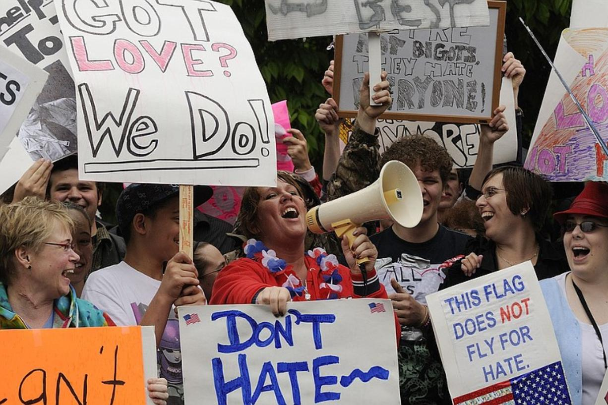 Kimberly Frost, center, uses a bullhorn to sing songs against a small number of Westboro Baptist Church members who picketed outside Heritage High School Tuesday.