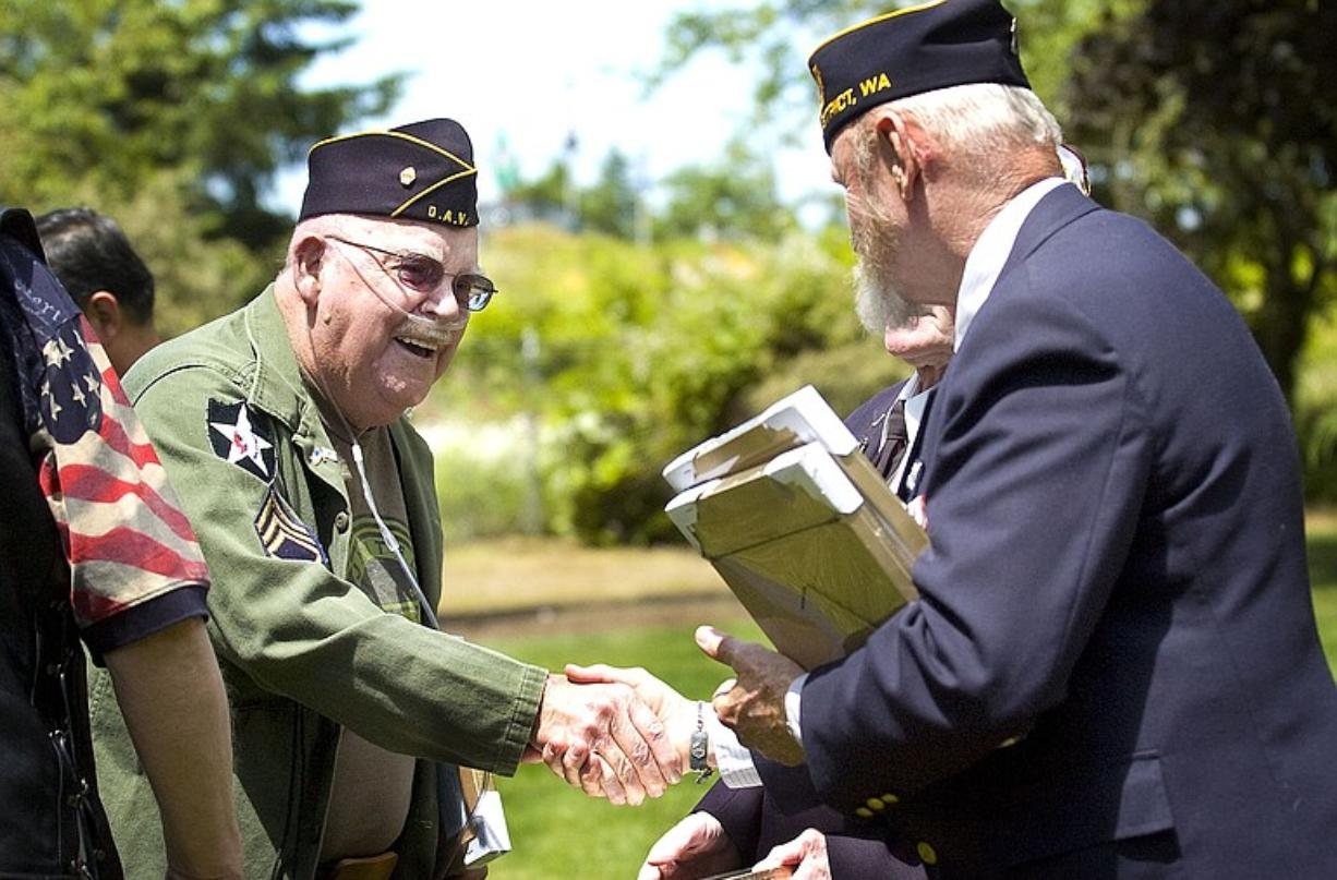 Will Hayden, left, a Korean War veteran, receives a plaque honoring his service Friday from the Rev. Jerry Keesee, American Legion chaplain. From June 25, 1950, to July 27, 1953, the U.S.