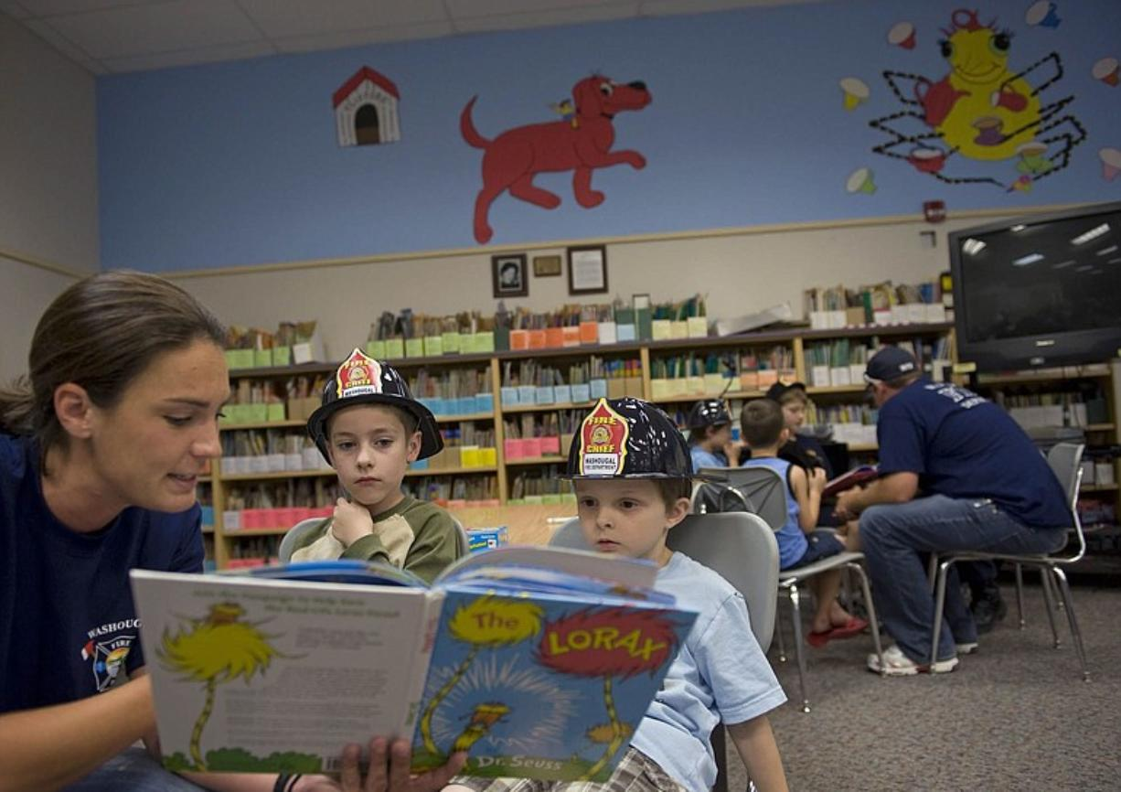 "Washougal Firefighter Carly Shears reads ""The Lorax"" by Dr. Seuss to first-graders Spencer Nicholson, center, and Riley Gardner. On Thursday, firefighters visited the 20 students who are participating in a six-week summer literacy program at Hathaway Elementary School."