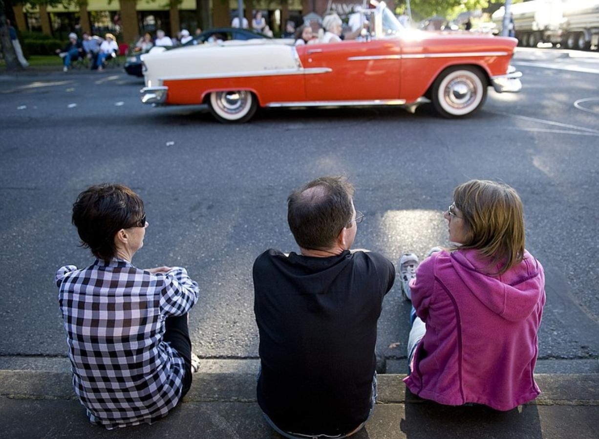 From left, Shirley Fire, Dan Herrick and Paula Gardner, all of Vancouver, watch vintage cars drive along Main Street on Saturday evening.