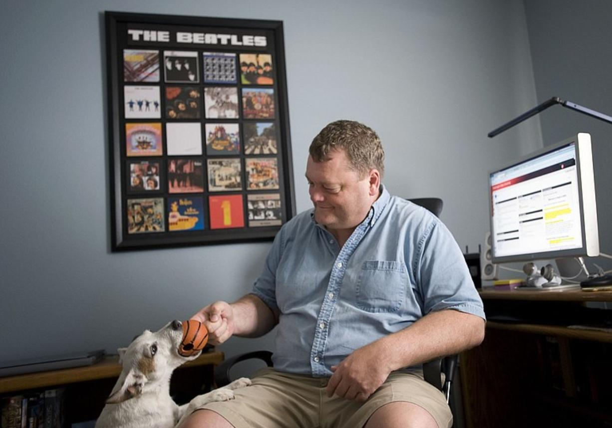 Jason Spicer, 48, a Washington State University online student, plays with his dog Zaika near his home computer in Washougal. The former Microsoft employee will finish a business degree this semester, without once visiting Pullman.
