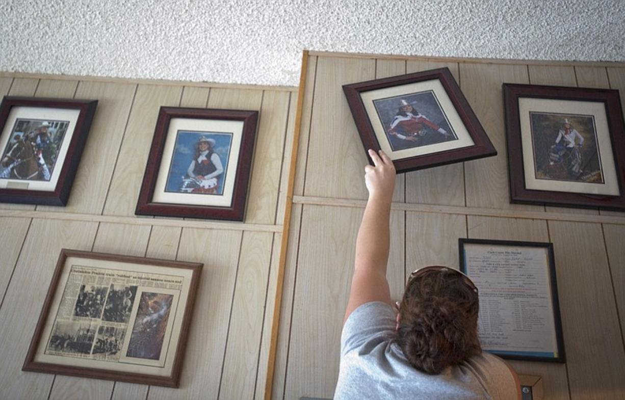 Vancouver Saddle Club member Sarah McKinzie hangs Tegan Rushworth's 2003 Fort Vancouver Rodeo queen portrait inside the Clark County Saddle Club Thursday. Vancouver Officer Erik McGarrity is on paid administrative leave while police internal affairs investigates his relationship with Rushworth, who served as a paid drug informant for him.