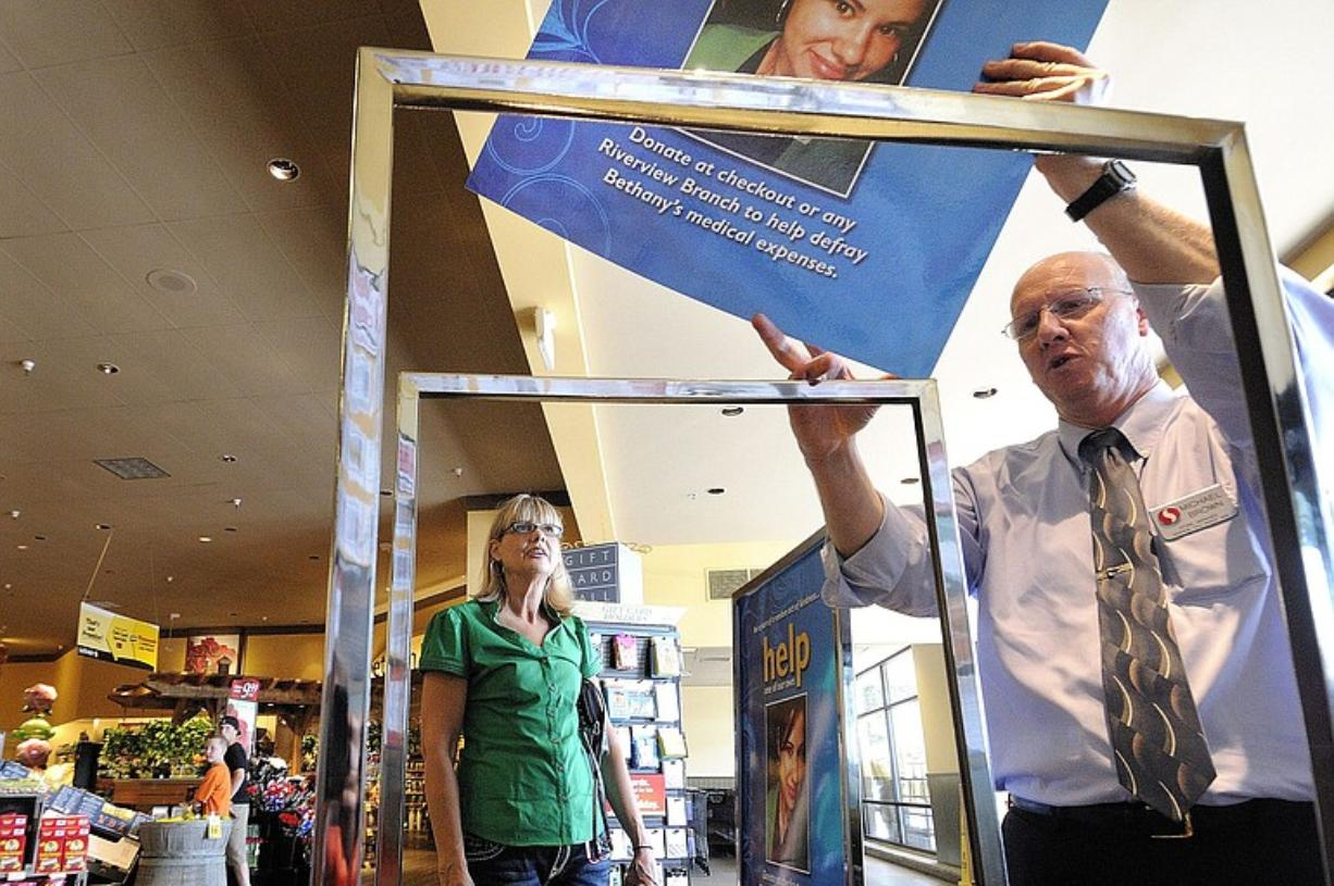 Michael Brown, right, a manager at the Safeway store in Washougal where Bethany Storro worked at the deli counter, places poster in display stands Friday as Nancy Neuwelt, Storro's mother, watches.
