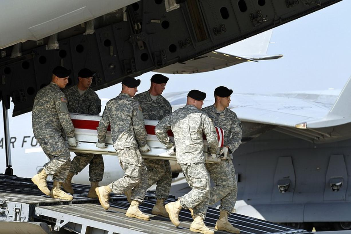 An Army carry team carries the transfer case containing the remains of Army Chief Warrant Officer Jonah D. McClellan of Battle Ground upon its arrival at Dover Air Force Base in Delaware on Wednesday.