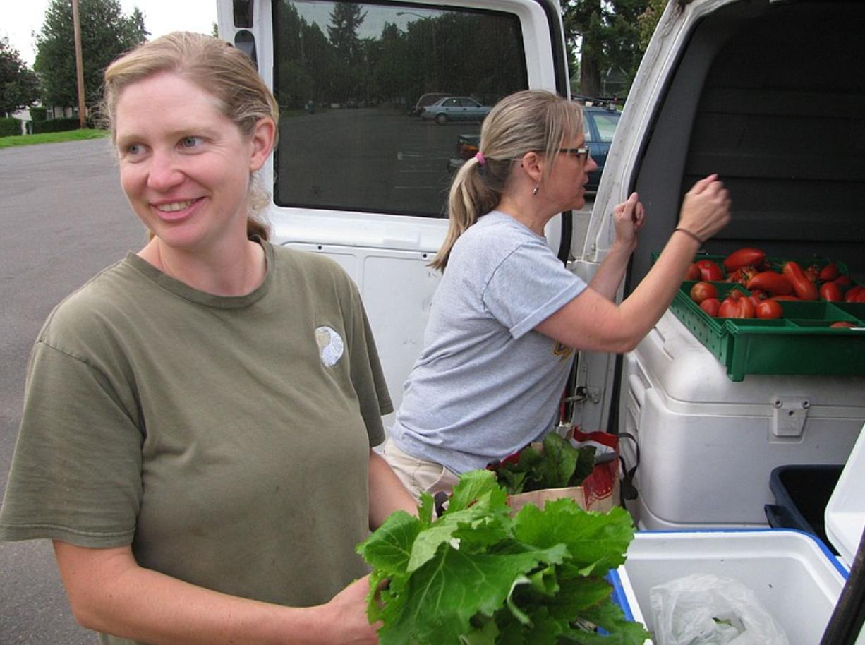 April Jones, an organic CSA farmer from Ridgefield, left, distributes fresh produce to Fruit Valley resident Michelle May. Jones now delivers several CSA shares to the Fruit Valley neighborhood.