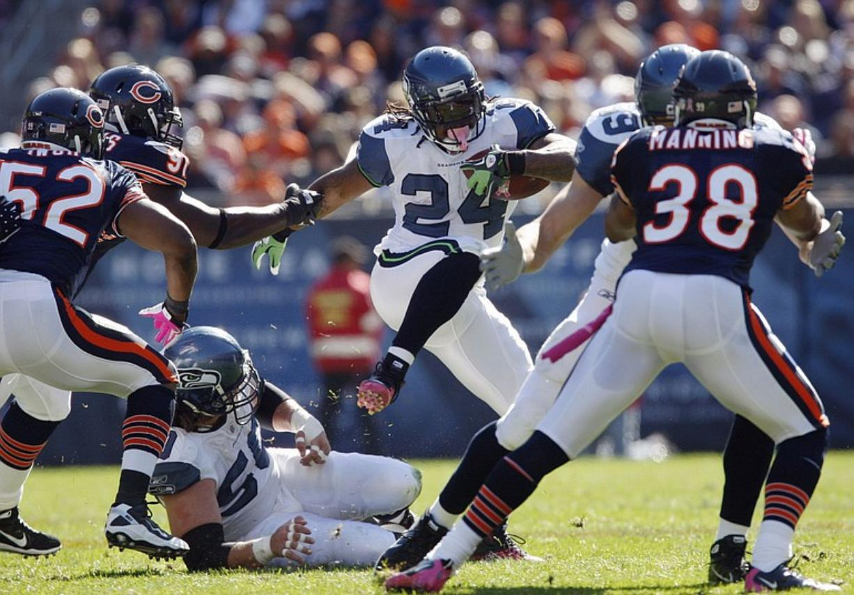 Seattle Seahawks running back Marshawn Lynch (24) gains yards as Chicago Bears defenders Brian Iwuh (52), Tommie Harris (91) and Danieal Manning (38) close in during the first half Sunday.