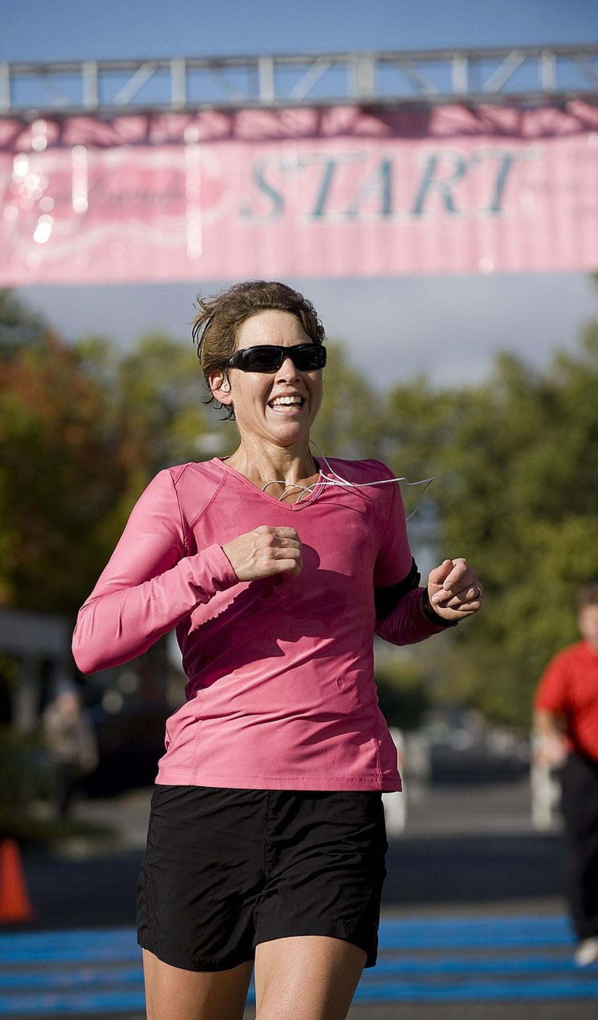 Meg Godfrey, from Lake Oswego, Ore., is the first runner across the finish line at the fourth-annual Girlfriends Half Marathon in Vancouver on Sunday.