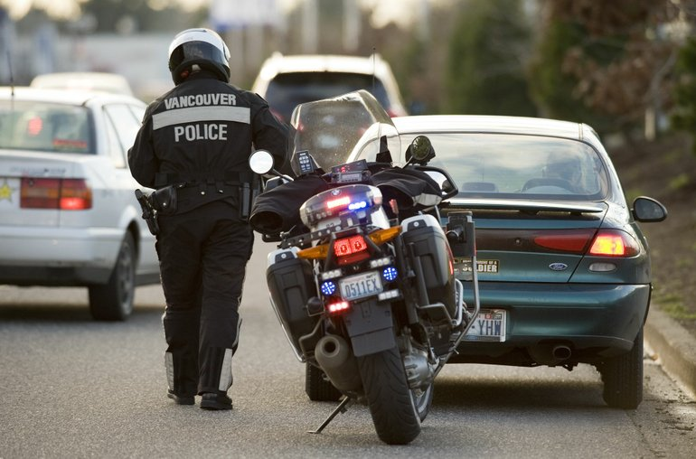 Vancouver Police Officer John Davis issues a speeding ticket to a driver.