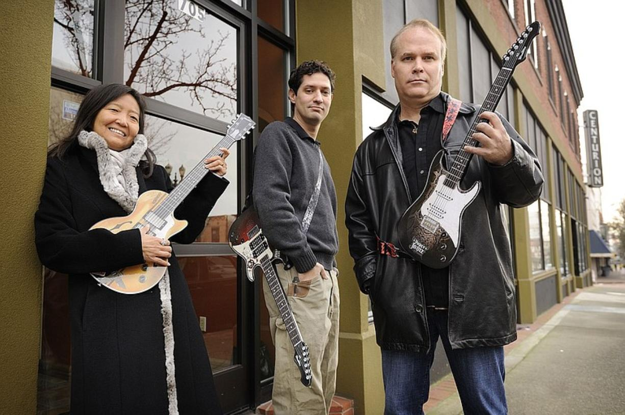 Pure Imagination LLC partners, from left, Miriam Kim, Philip Odom and Mike Wallace hold their top-selling toy, the Paper Jamz electric guitar, outside their new downtown Vancouver office.