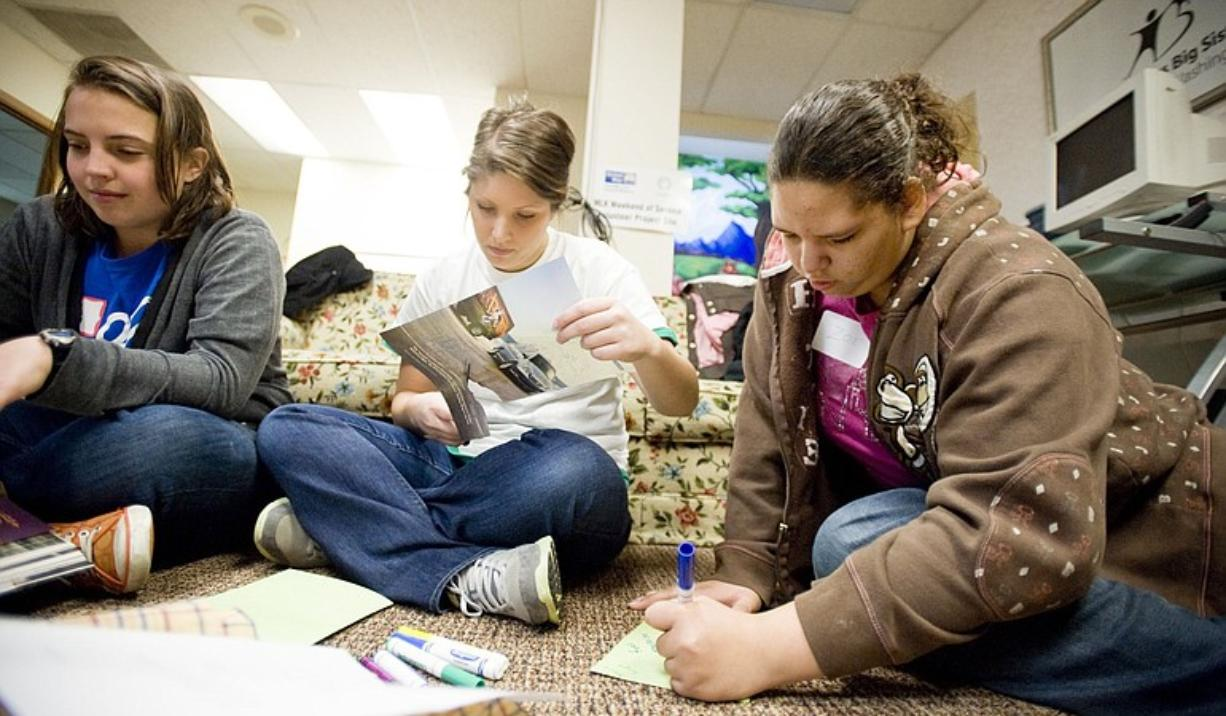 Zoe Brown, a 13-year-old Covington Middle School student, right, with volunteers Annie Burnette, left, and Kaitlynn Jaeger make cards for the homeless during the United Way's Martin Luther King Jr.