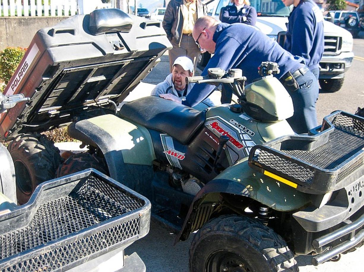 Jeff Haxby, kneeling at left, checks out the rear dump bed of a six-wheel-drive Polaris all-terrain vehicle on Wednesday with Maury Hildenbrand, a medic with Skamania County Emergency Medical Services. Haxby works for the Bonneville Power Administration, which donated six used ATVs to help with rescue missions in Skamania County.