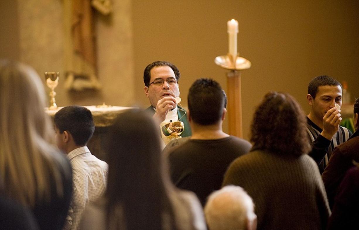 Father Armando Perez gives communion during a Spanish-language mass at St. John the Evangelist Catholic Church on Sunday.