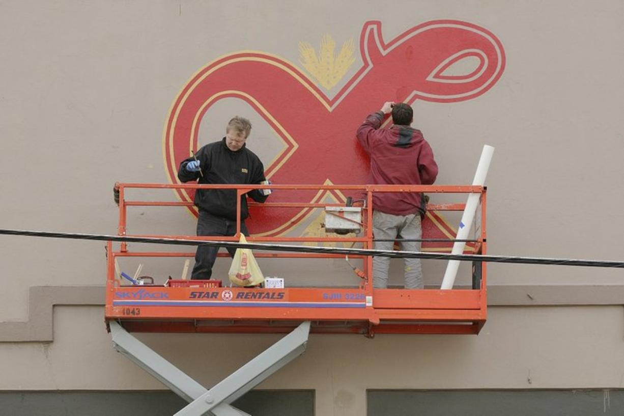 Heath Dewallace and Mike Starks of Soha Signs in Vancouver paint a replica of the Lucky Lager logo that once towered over downtown Vancouver.