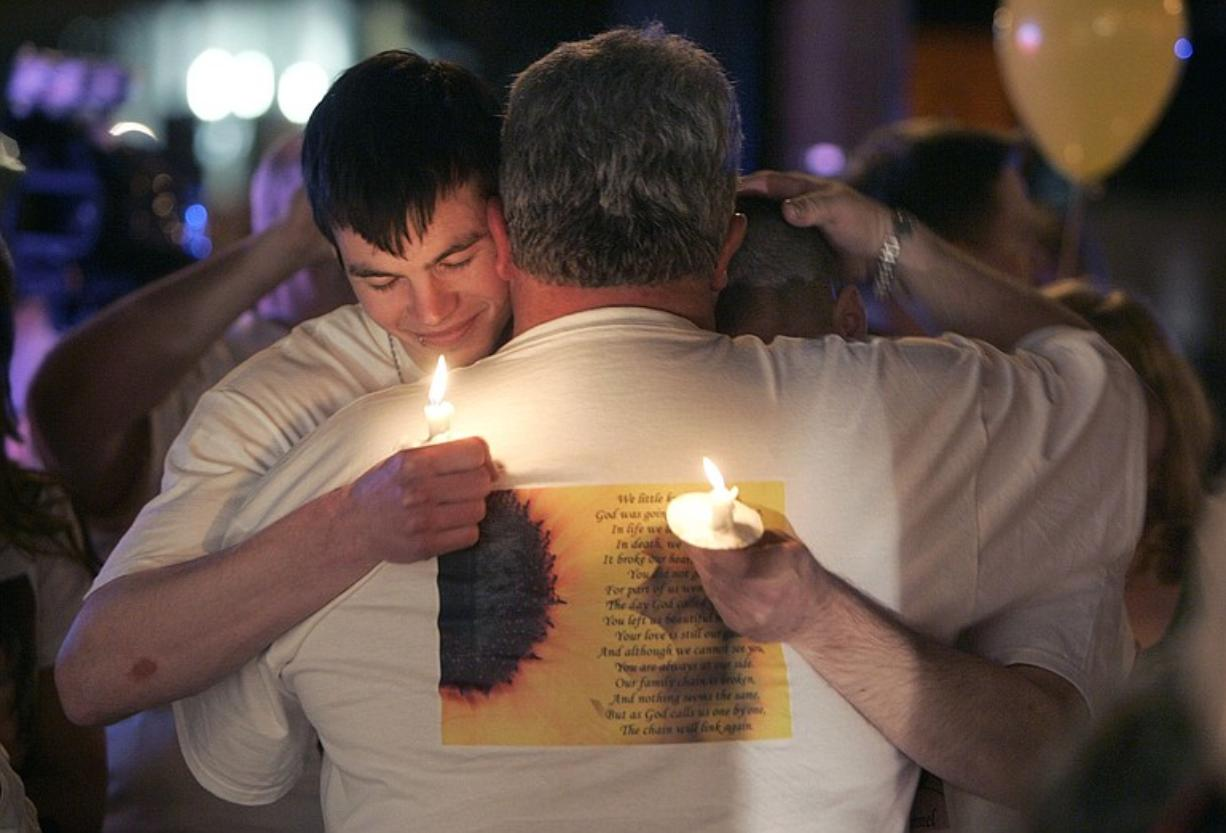 Erik Gittings, on left, and Dan Marciano hug Danielle Sale's father David Sale at the first anniversary memorial of Danielle's death.