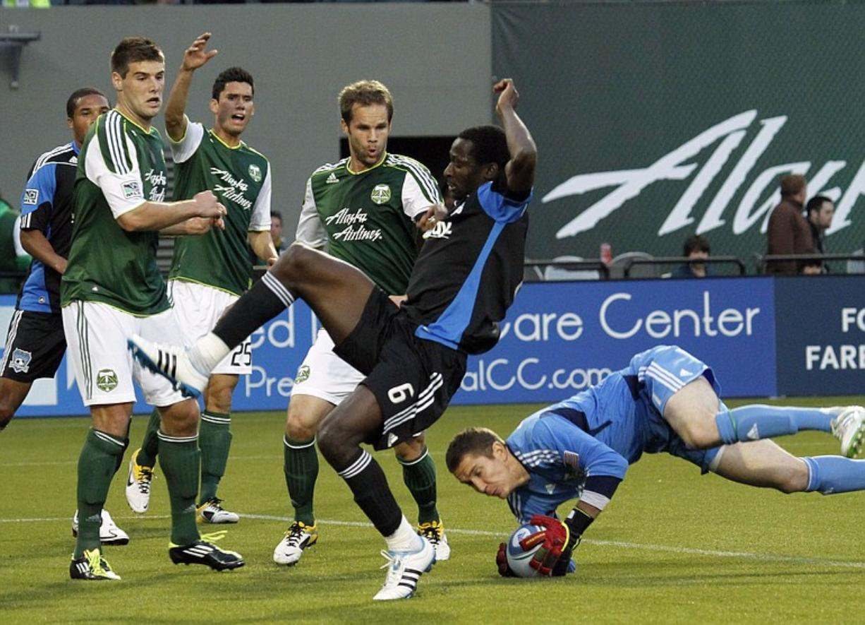 Timbers defenders, from left, David Horst, Steve Purdy and Freddie Braun watch as Timbers goalkeeper Troy Perkins, right, dives in to stop a shot by San Jose Earthquakes defender Ike Opara (6).