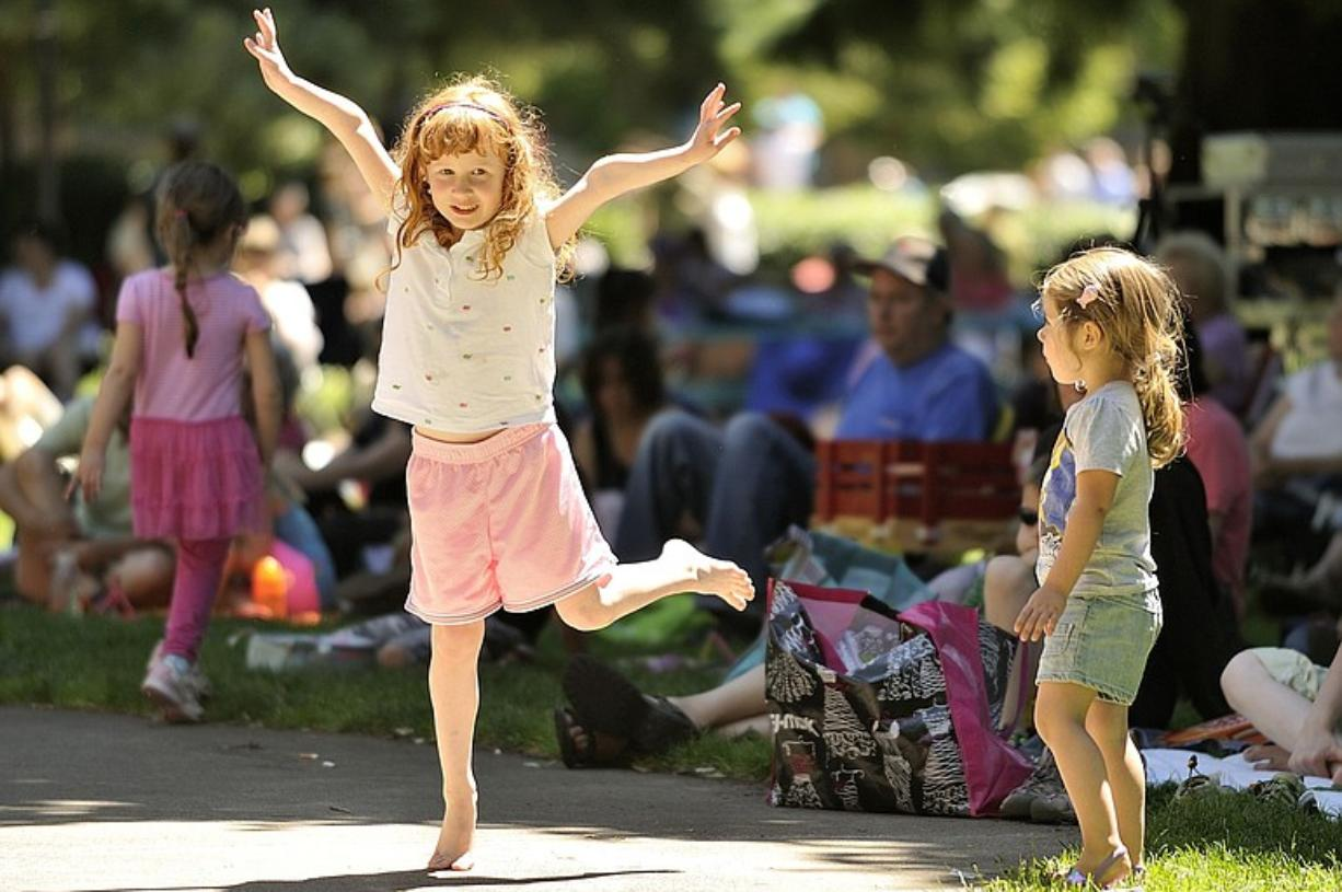 Sabrina Prill, 5, dances as Stella Henderson, 3, watches Wednesday at a noon concert in Esther Short Park in downtown Vancouver.