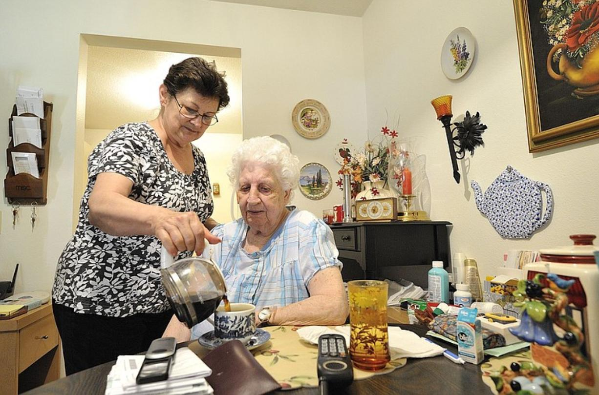 Caretaker Jean Bray, 66, left, pours a cup of coffee for her client, Jean Prew, 90, last week at Prew's home in Vancouver.