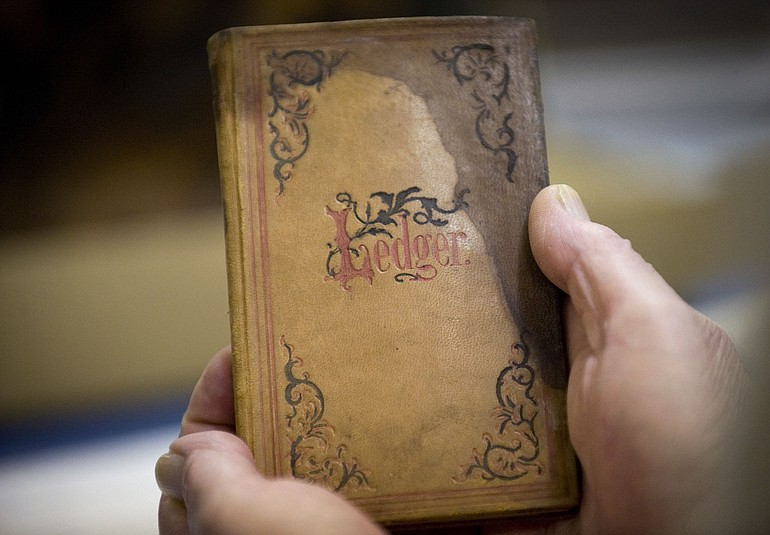 Richard Reay, a Clark County Historical Museum volunteer, holds a leather-bound book used as a diary