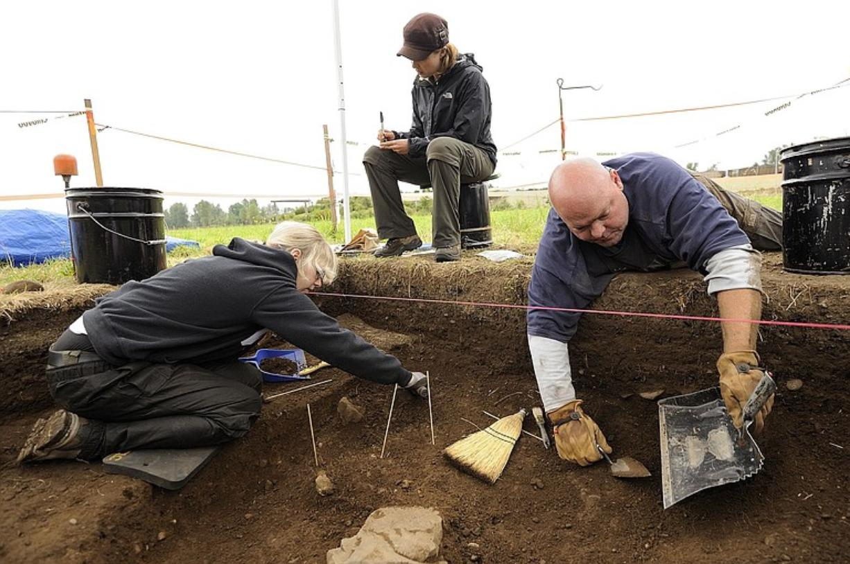 Cara O'Neil, center, a Portland State University grad student, logs information while WSU Vancouver student Sarah O'Keefe, left, and Bruce Schneider, a Northern Arizona University grad student, carefully excavate at a site in the workers' village Tuesday at the Fort Vancouver National Historic Site.