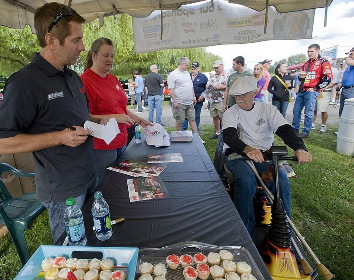 Vancouver driver Greg Biffle, left, signs a hat for Vancouver fan J.B. Selkregg during Wednesday's event at Portland International Raceway.