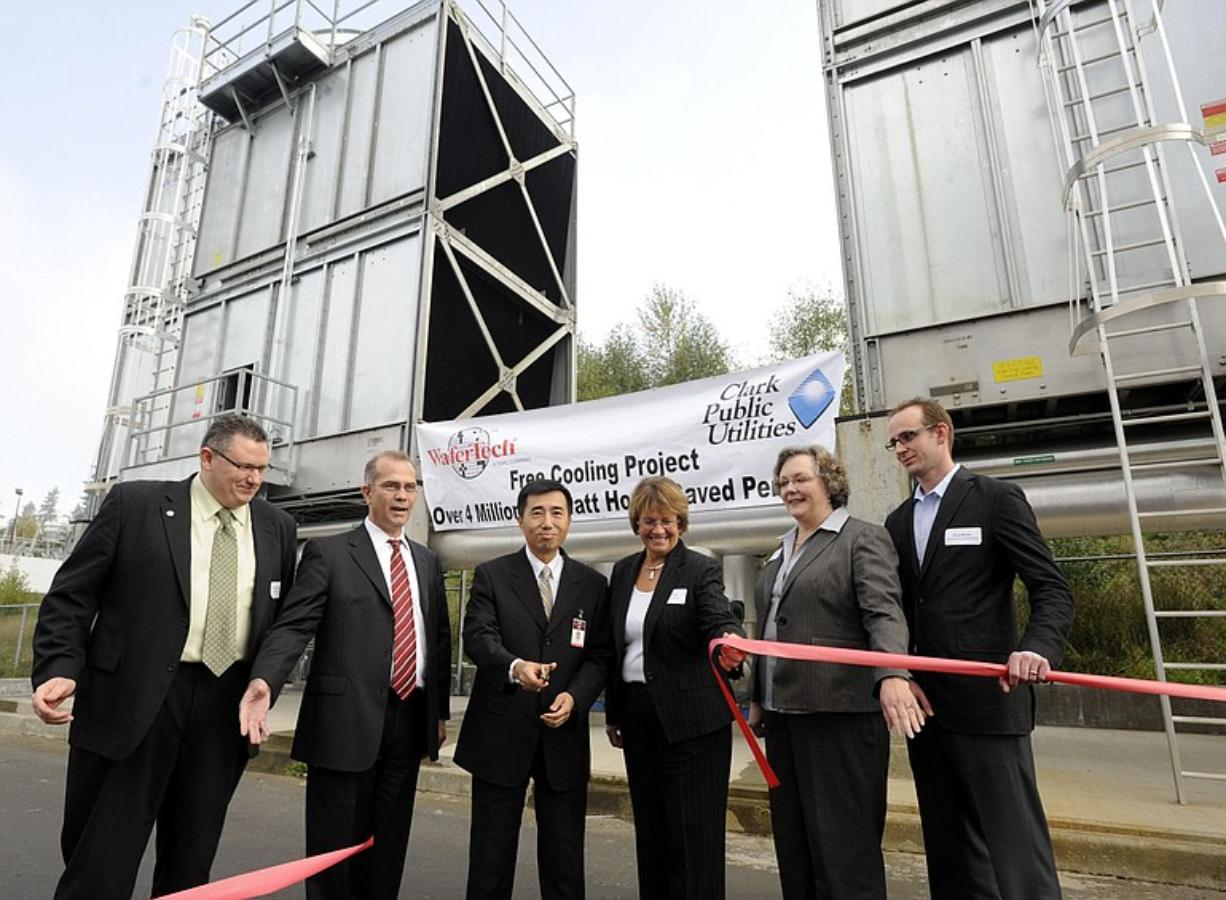 At a ceremony to dedicate new cooling towers at WaferTech, company President KC Hsu, center, cuts the ribbon with help from Camas Mayor Scott Higgins, from left, Sen.