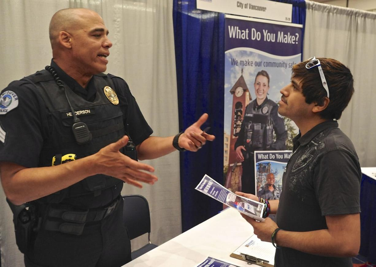 Sgt. Dave Henderson speaks with Frankie Cordova about job opportunities at Vancouver Police Department at a recent Hispanic Job Fair in Portland.