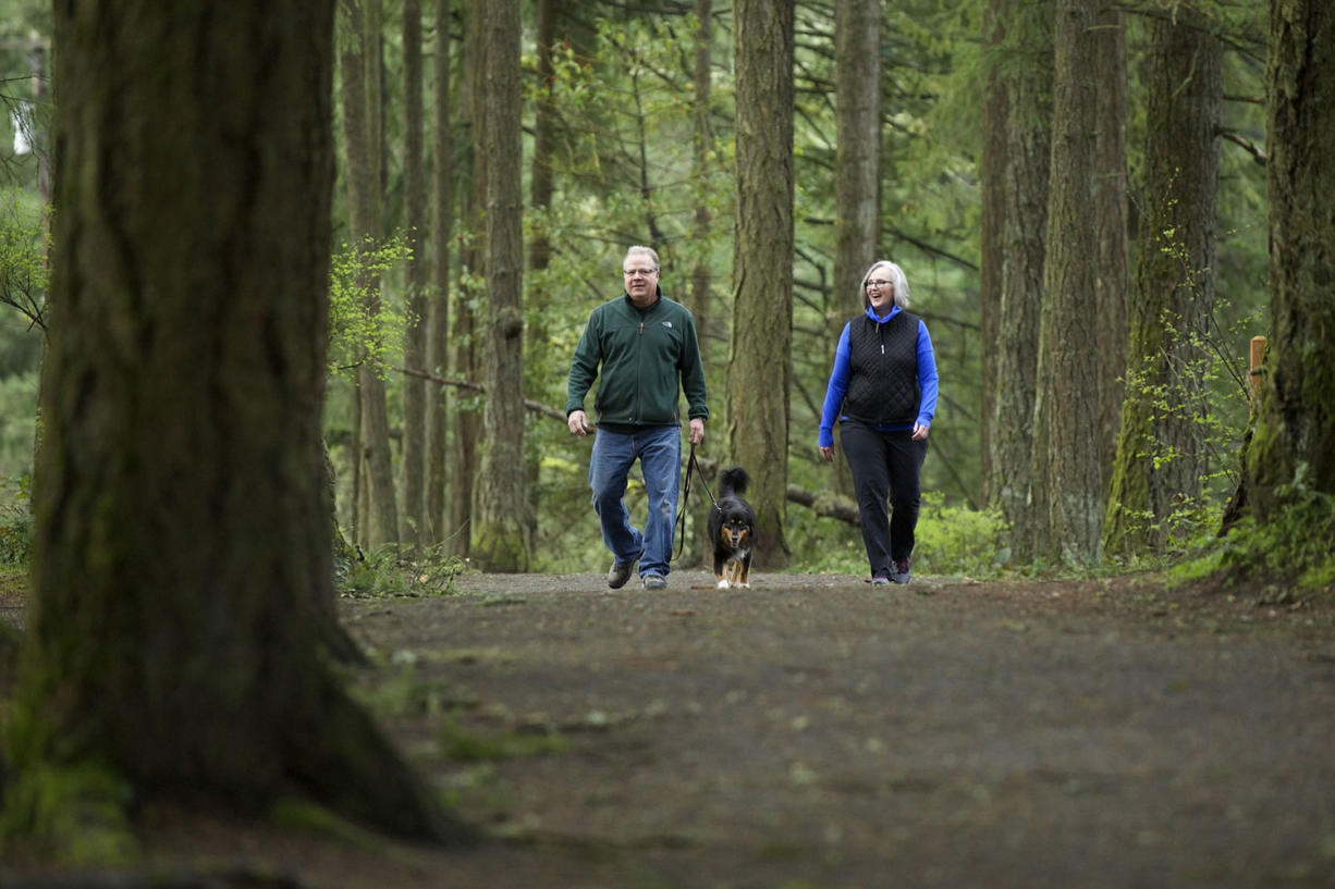 Camas residents Helen and Jay Elder, and their dog, Wesley, walk the trails along Round Lake on Wednesday. The Elders started walking daily at the urging of their chiropractor.