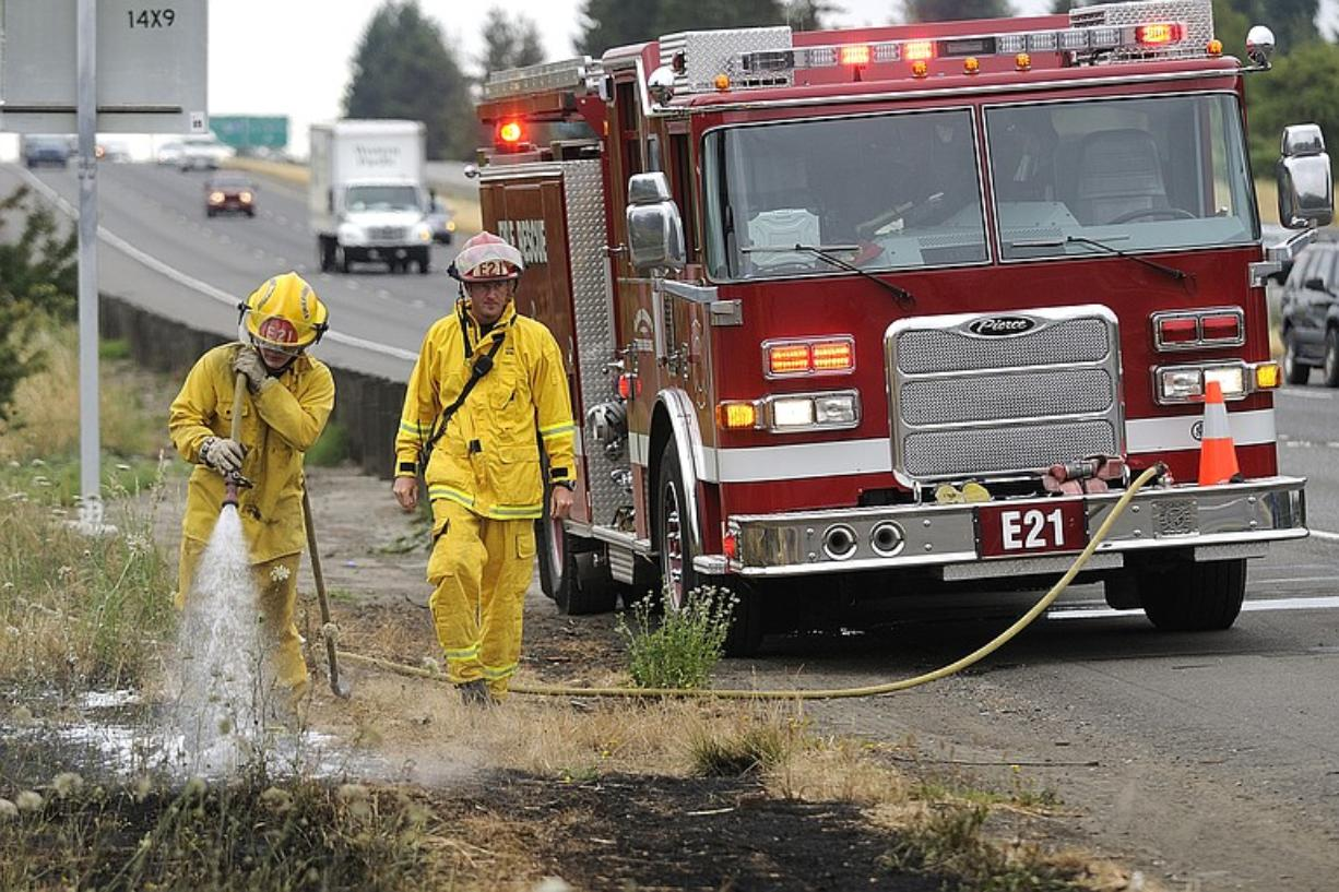 Volunteer firefighter Tyler Edwards, left, and Captain Ryan Berg, right, of Clark County Fire and Rescue extinguish one of a series of grass fires that broke out before 10 a.m. Friday along northbound Interstate 5.