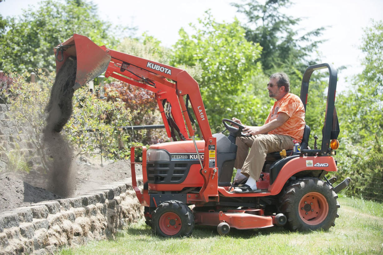 Rick Dobson uses a tractor to work in his yard at his home in Kalama.