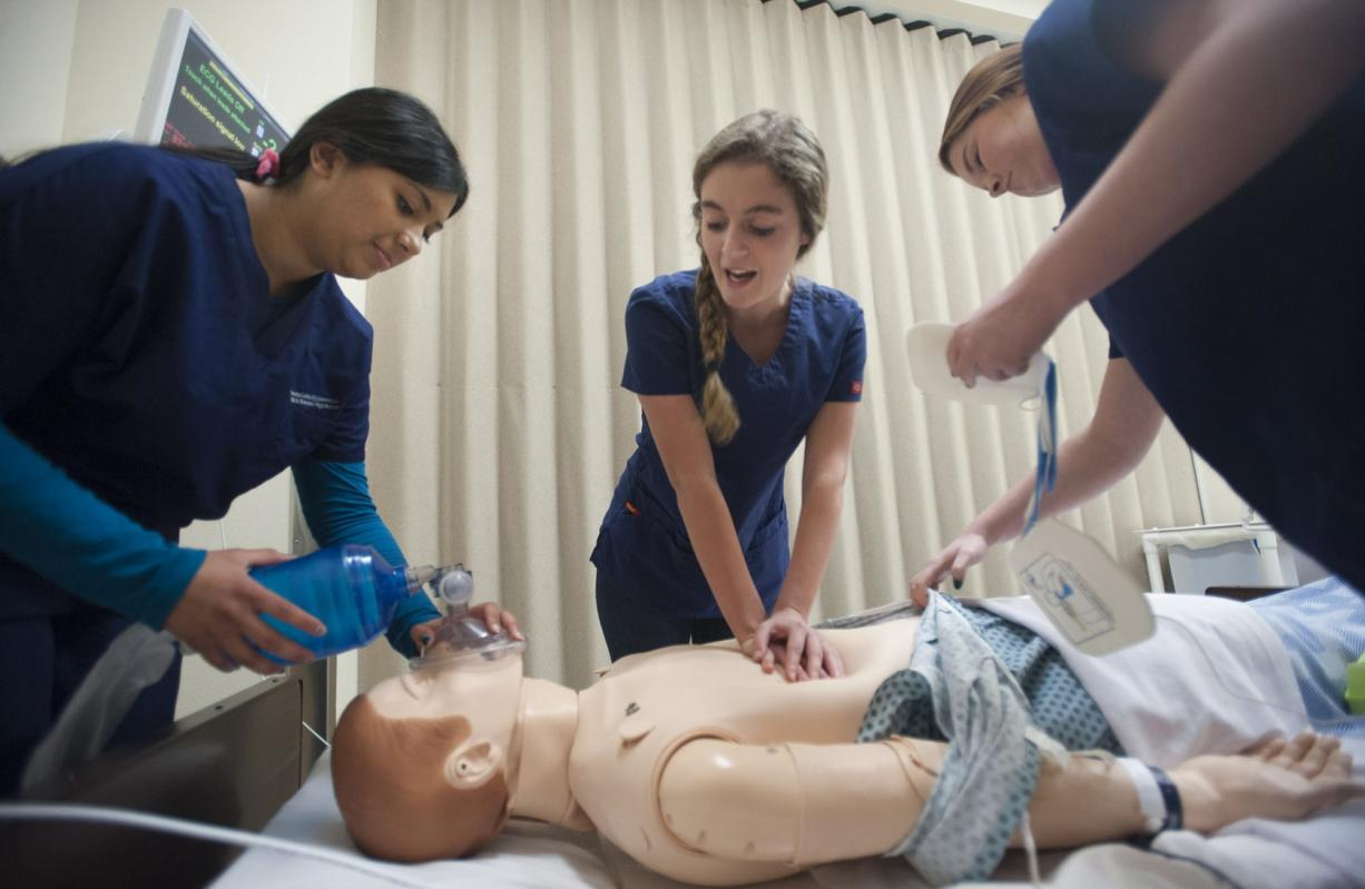 Nursing students Imrin Uppal, from left, Olivia Schmitz and Averie Henry practice monitoring and responding to patients in the state-of-the-art nursing station at Henrietta Lacks Health and Bioscience High School in Vancouver on Thursday.