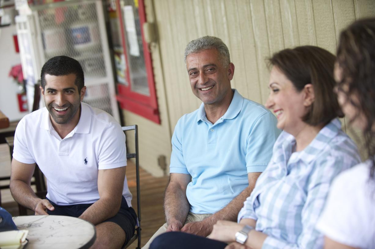 Kourosh Zamanizadeh, from left, and his parents, Mike and Rose Zamanizadeh, sit on the Skamania General Store's porch with store manager Michelle Sobaski, right.